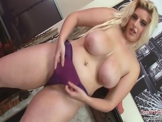 Curvy blonde chick Raphaella Lily stripping to show off her giant boobs and...
