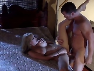Stormy Daniels is on the bed with a guy. She is naked and he is naked as...