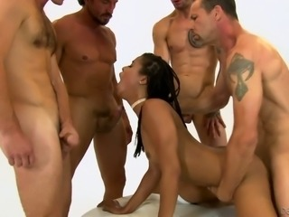 Marvelous and slender black girl on her knees surrounded with big dicks
