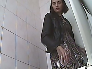 Brunette hot woman in the public restroom recorded from behind