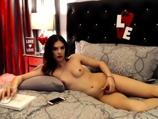Enticing shemale with small boobs masturbates on the bed